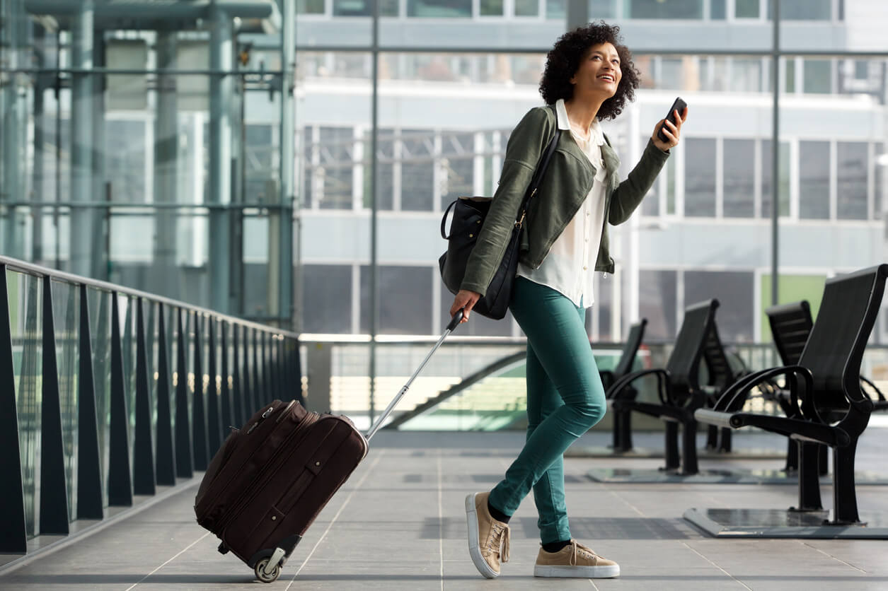 Woman walking through airport and carrying suitcase