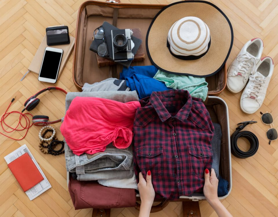Person packing a suitcase for vacation