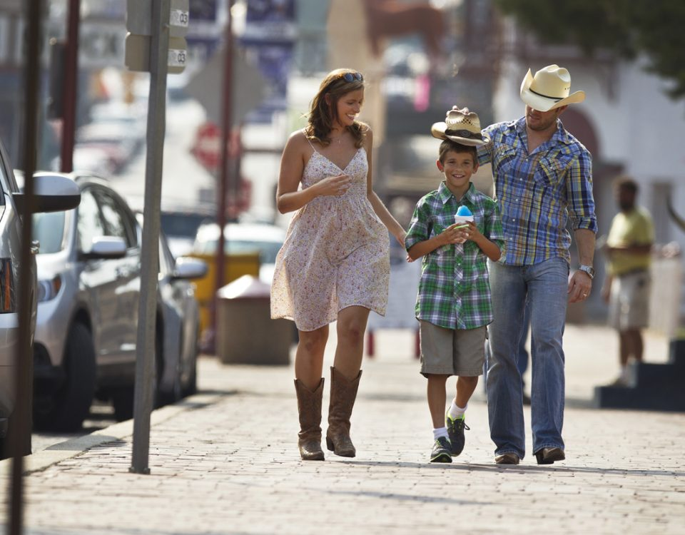 happy western family strolling down street while on vacation