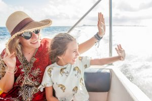 mother and daughter smiling while on boat tour during summer vacation